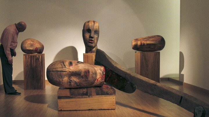 A large wooden sculpture by Mustafa Al depicts heads severed by an axe.