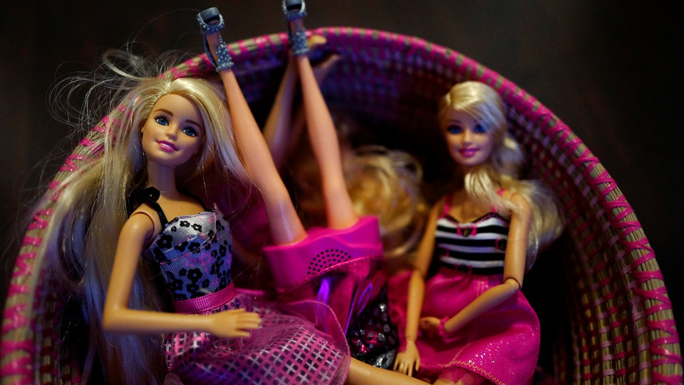 Barbie dolls sit in a basket