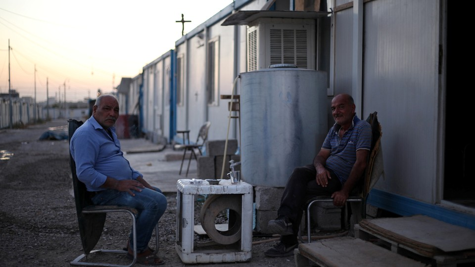 Christian men are seated outside a trailer at the Ankawa refugee camp in Erbil, Iraq, on September 12, 2018.