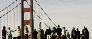 A group of people stand on a hill overlooking the Golden Gate Bridge