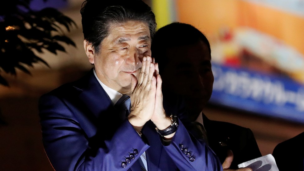 Prime Minister Shinzo Abe closes his hands in thanks at a campaign rally.