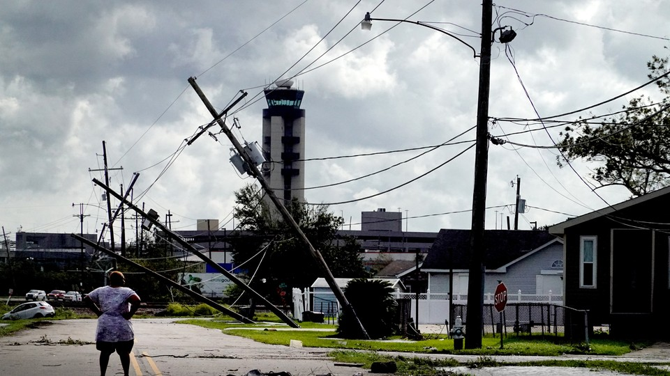 A woman looks over damage to a neighborhood caused by Hurricane Ida on August 30, 2021, in Kenner, Louisiana.