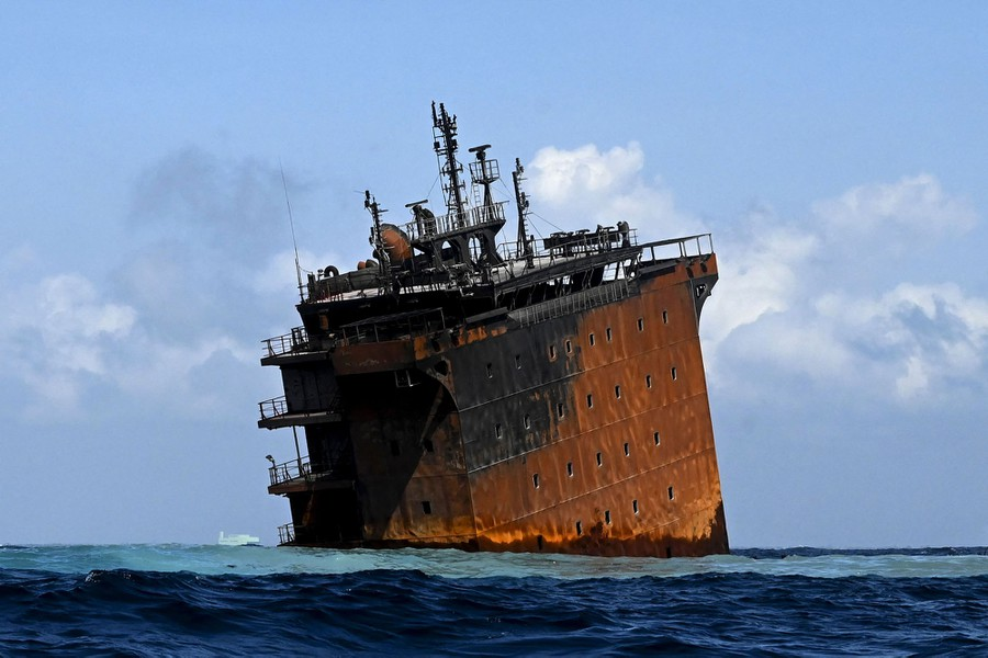 Part of the burned ship is still visible as the vessel slowly sinks.