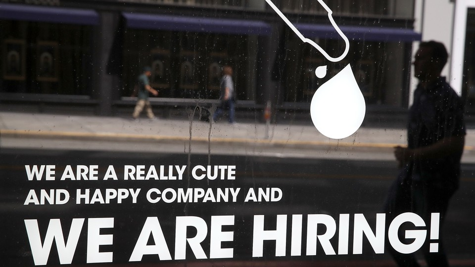 A man walks by a window with a hiring ad printed on it.