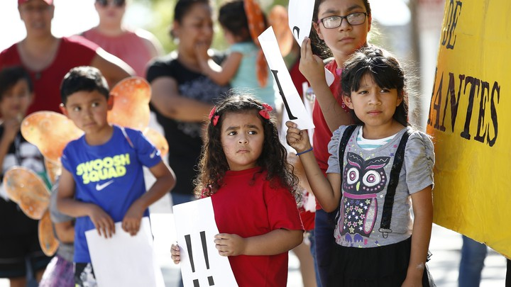 Children listen to speakers during an immigration family-separation protest on June 18, 2018, in Phoenix