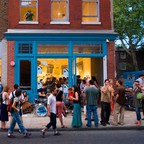 """People gather in the street near an open gallery in Philadelphia's Old City neighborhood for a """"First Friday"""" event."""