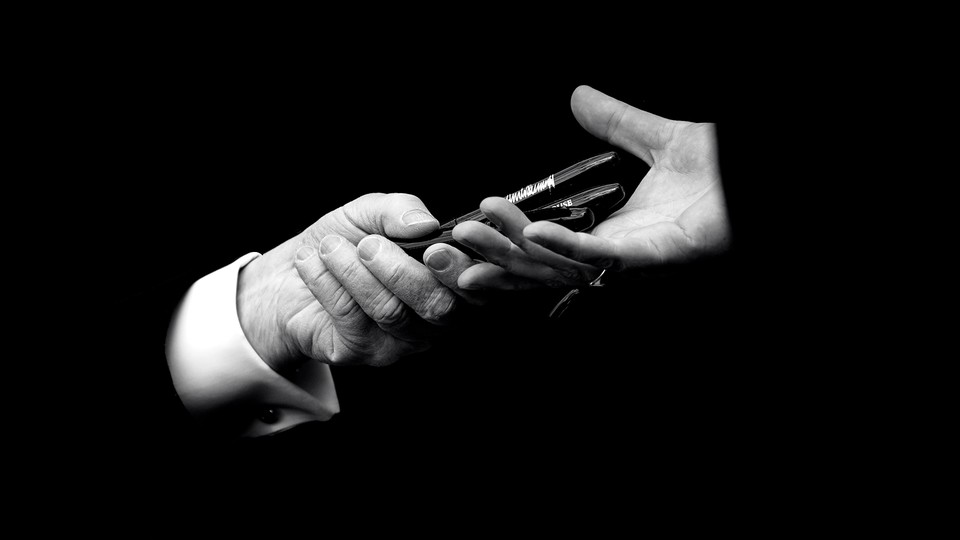 A black-and-white image of pens being exchanged from one hand to another