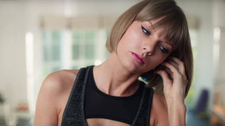 Taylor Swift adjusts her headphones in an Apple Music ad