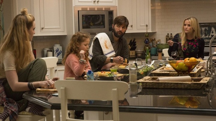 """A screenshot of """"Big Little Lies"""" featuring the actress Reese Witherspoon and her characters' husband and children."""