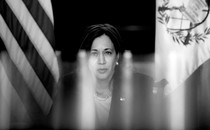 A back-and-white photo of Kamala Harris framed by American and Guatemalan flags behind her