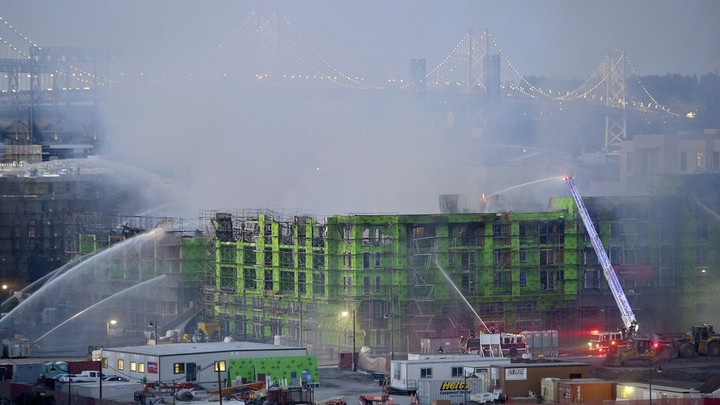 Firefighters spray water on a burning, partially completed apartment building in the San Francisco Bay Area.