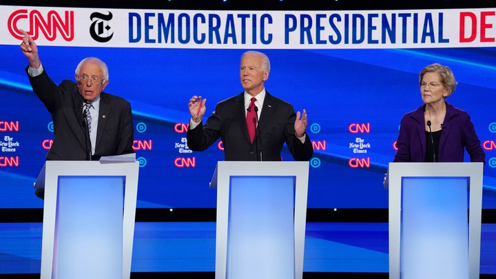 Vermont Senator Bernie Sanders, standing next to former Vice President Joe Biden and Senator Elizabeth Warren of Massachusetts, all behind lecterns on a stage, raises his hand during the fourth Democratic primary debate.