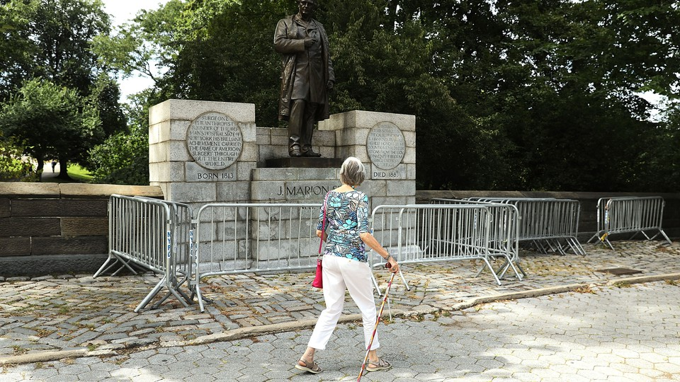 A woman with a cane walks past the J Marion Sims statue in New York's Central Park.