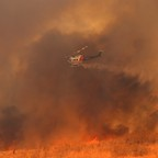 A helicopter drops water on a wind-driven wildfire in Orange, California, on October 9, 2017.