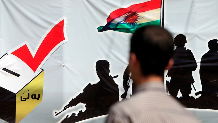 A man looks at a banner supporting the referendum for independence of Kurdistan