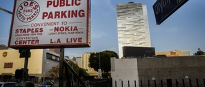 a sign advertising public parking next to a large building