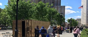 People mill around in front of a gold-painted shipping container, part of the Portals Project, where they can share experiences around policing with residents around the world.