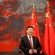Chinese President Xi Jinping  sits in a chair in front of two Chinese flags.