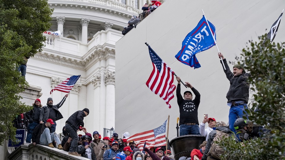 Trump supporters wave flags at the Capitol January 6.