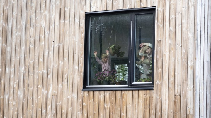 Three children stare out a window.