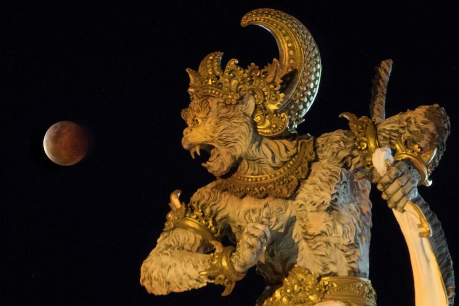 The moon is seen beyond an ornate sculpture.