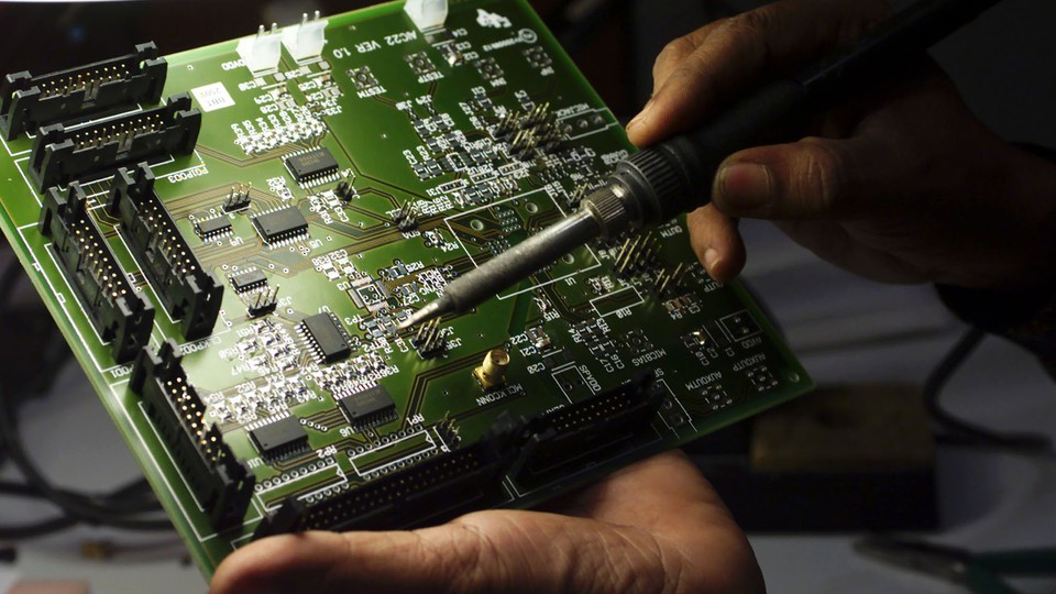 A technician works on a computer electronics component