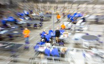 A blurred photo of groups of people in blue shirts sitting at tables during the recount in Arizona. A few people in orange shirts are dotted around the room.