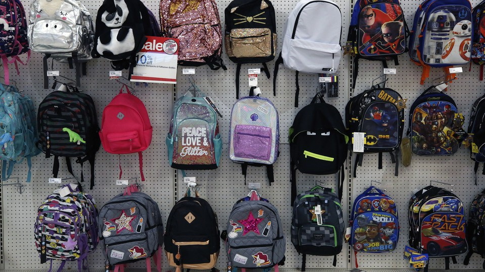 Rows of backpacks hang in a store