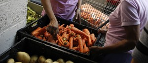Carrots, corn, and potatoes are piled at a food bank