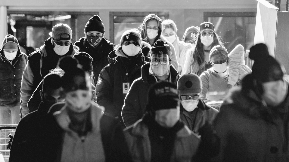 People stand together wearing masks and bundled in warm clothing.