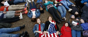 "Eleanor Nuechterlein, 16, hold hands with her mother as they participate in a ""die-in"" during a protest in favor of gun control reform in front of the White House, Monday, Feb. 19, 2018."