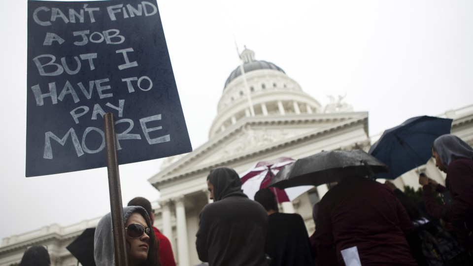 """Woman stands with a sign that reads """"Can't find a job but I have to pay more"""" in California"""
