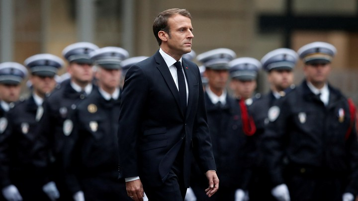 Emmanuel Macron walks past a line of police officers in formation during a ceremony to honor the four victims of the Paris police-headquarters killings.