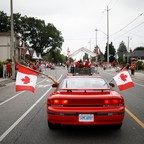 People hold Canadian flags with hockey sticks from inside a car during the East York Toronto Canada Day parade, as the country marks its 150th anniversary