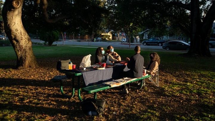 A family eating holiday dinner outside.