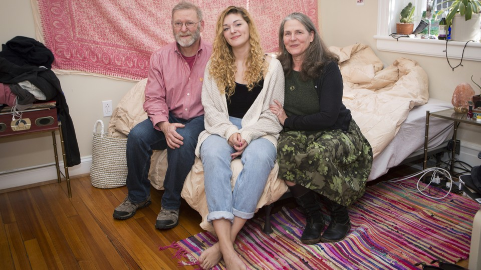Two parents and their young adult daughter sit on a bed in a college apartment.