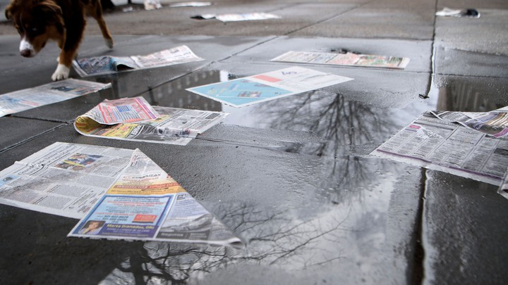 A discarded newspaper on the wet ground
