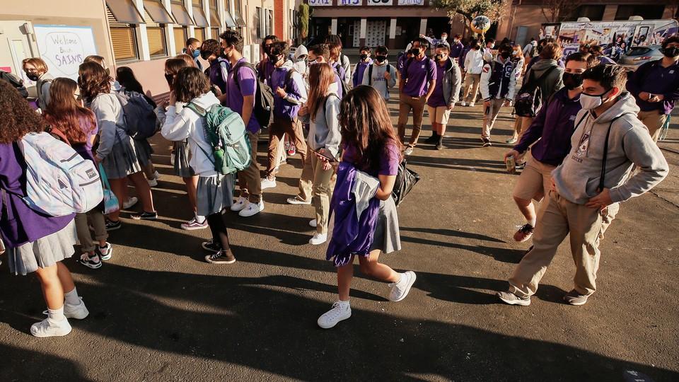 Students queue to enter school building in California.