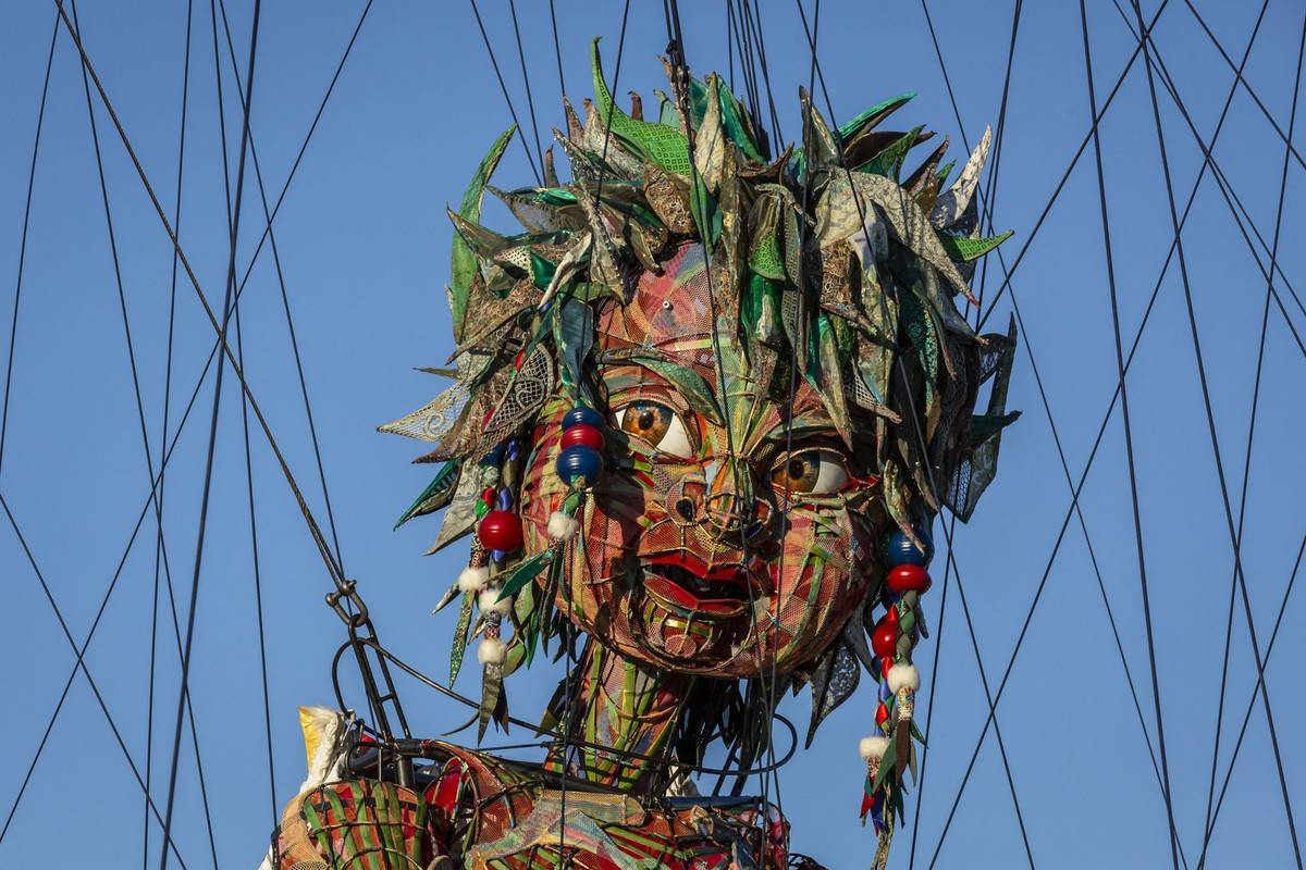 The head of a giant puppet is seen among cables.