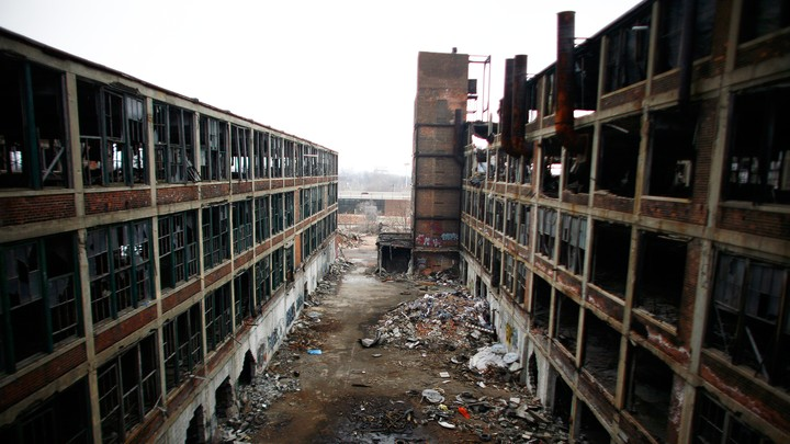 Area between two abandoned factories. Primarily brown in color. Windows are broken or missing altogether. There's debris on the ground. It's overcast.