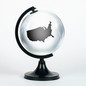 A transparent globe with an outline of the US contained inside it