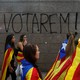 """Students wear Esteladas (Catalan separatist flag) during a demonstration in front of a graffiti on the wall that reads, """"We will vote!"""""""