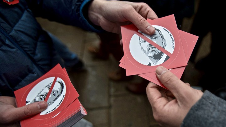 Anti-Kickl demonstrators hand out stickers with his face on them at a rally in Vienna in December 2018.