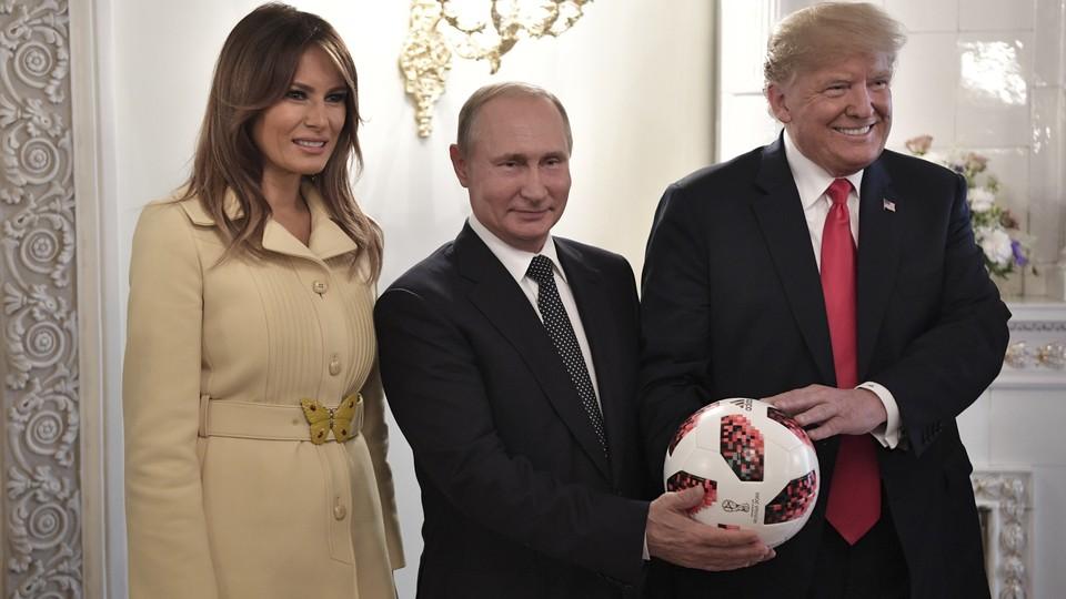 Melania Trump, Vladimir Putin, and Donald Trump pose with a soccer ball.