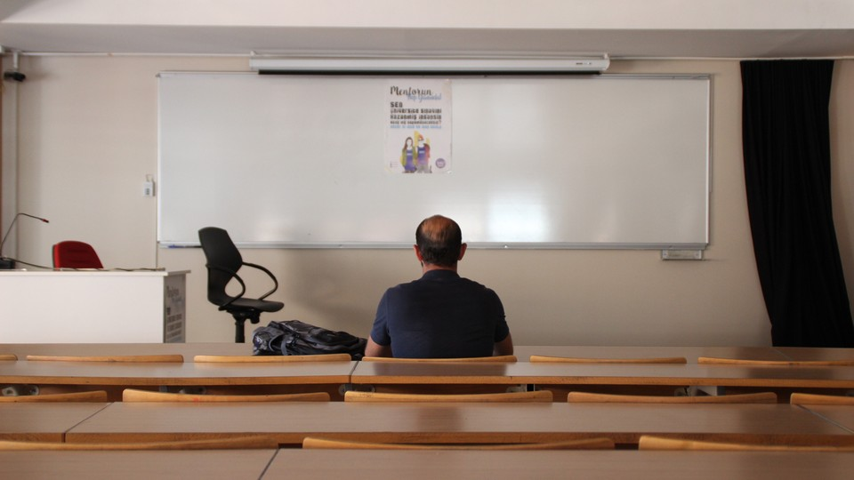 The back of a man sitting in an empty classroom, facing a blank dry-erase board