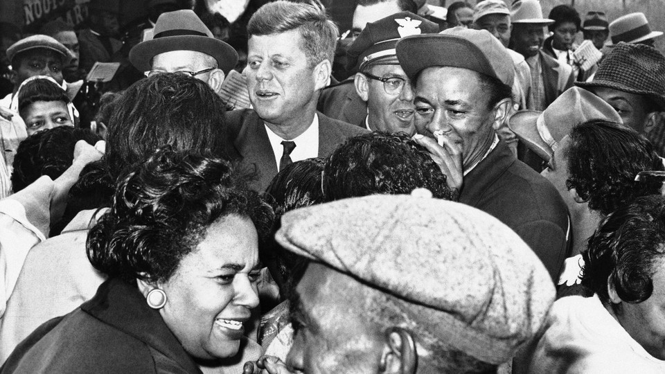 Kennedy greets residents of the all–African American community of Brooklyn, a suburb in Illinois, Oct. 3, 1960. He had not scheduled a campaign stop there. When he noticed a crowd had turned out with a brass band, he stopped and greeted many of them.