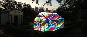 A tent-like pavilion with a colorful stained-glass design in a cemetery at dusk.