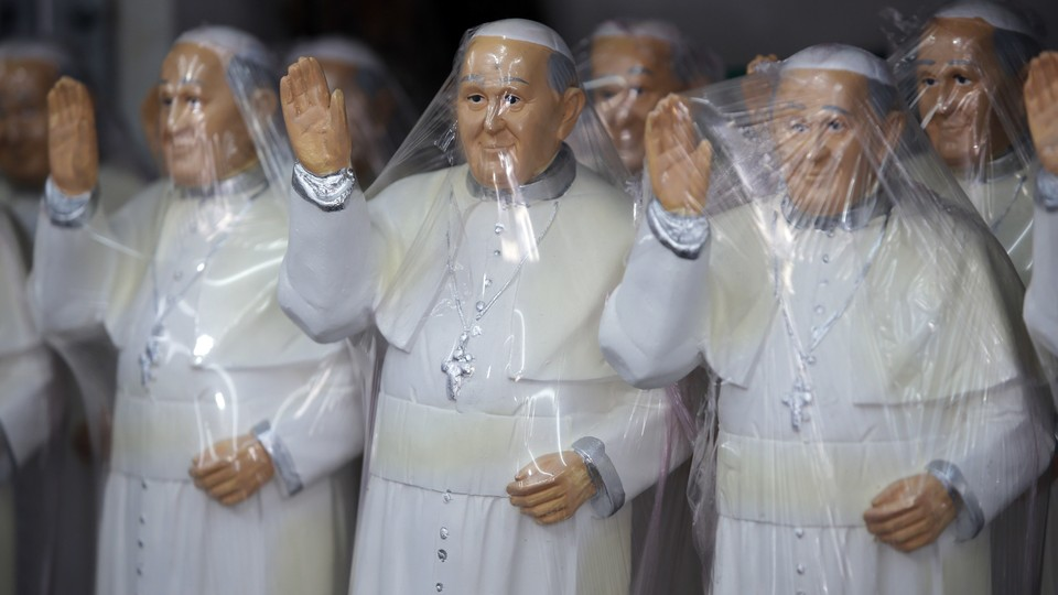 Plastic covered statues of Pope Francis stand for sale at a shop in Bogota, Colombia.