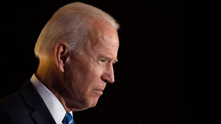 Joe Biden's head and shoulders are shown in profile against a black background.