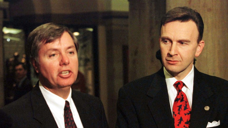 Then-Representatives Lindsey Graham and James Rogan speak with the press during the impeachment trial of former President Bill Clinton